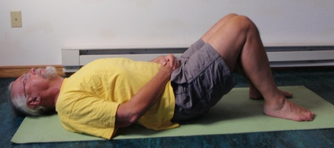 Coach John Hughes demonstrating bridging exercise for core training for cyclists