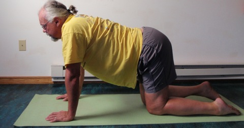 Coach John Hughes demonstrating kneeling back extension exercise for core training for cyclists