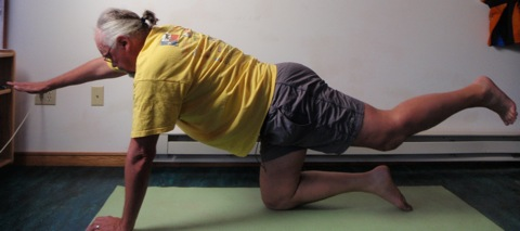 Coach John Hughes demonstrating kneeling back extension exercise for core training for cycling