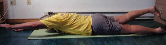 Coach John Hughes demonstrating lying back extension exercise for core training for cycling